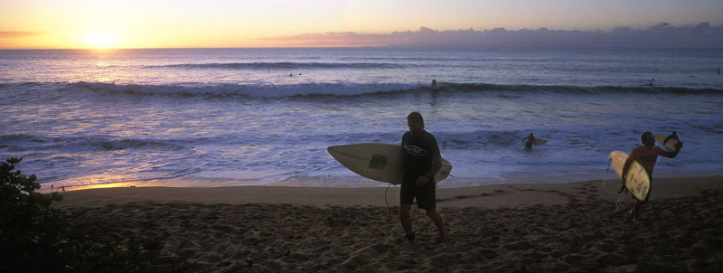 Surfers at Kepuhi beach leave the surf at sunset.