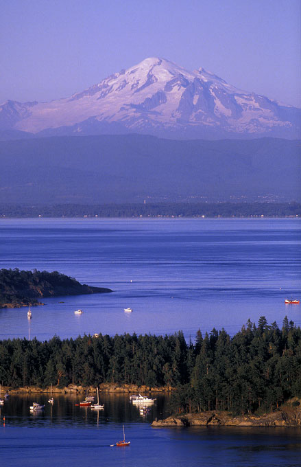 Shot on assignment for SUNSET magazine.  Late afternoon summer aerial view of Sucia Island in the San Juan Islands of Northern Puget Sound  Sucia is the holy grail for cruising boaters in the Pacific Northwest.  The entire island is a marine state park accessible only by private boat. Snowcapped Mount Baker stands guard in the background.