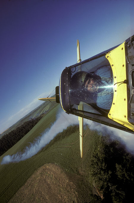 Shot for NATIONAL GEOGRAPHIC Magazine. Pilot Craig Fountain releases a stream of smoke to test for wind drift before spraying his load of agricultural chemicals.  This photo was taken using a remote camera attached to the upper wing of the Gruman Ag-cat biplane and triggered by a radio transmitter.