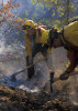 A fire crew from North Carolina cuts line and stamps out hot spots on the Bear Fire in western Montana.
