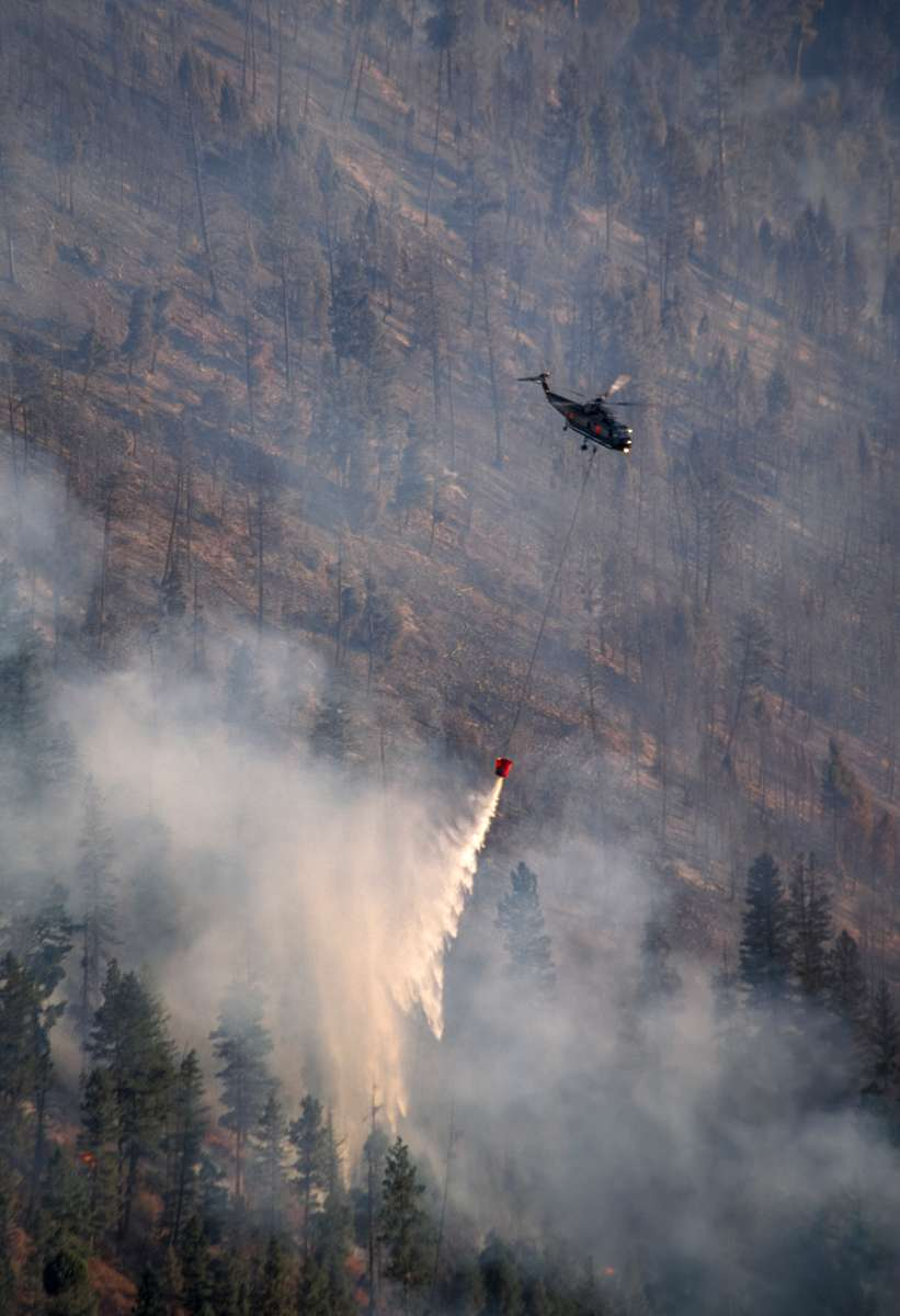A helicopter makes a late afternoon water drop on the eastern flank of the Bear Fire.