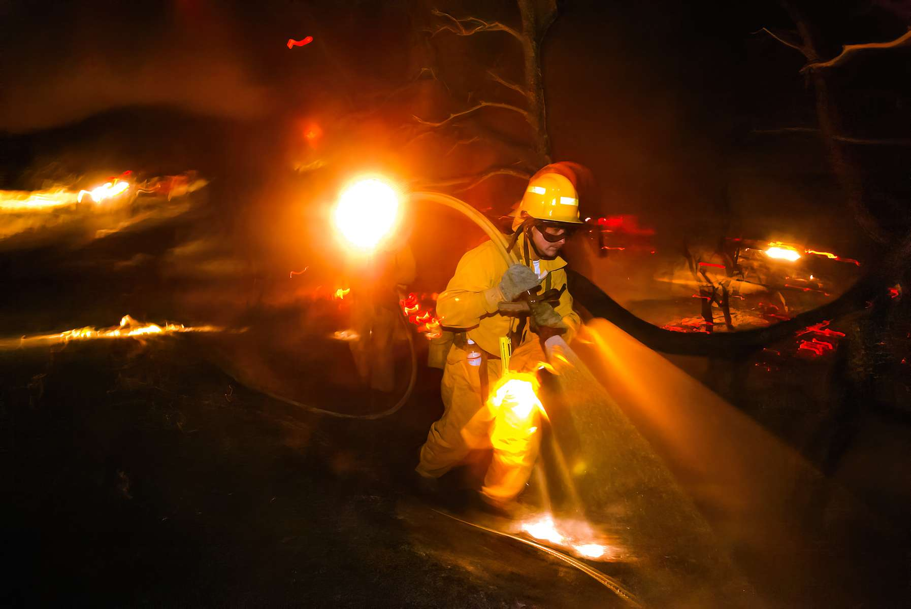 Firefighter Paul Shikowitz of the Dry Creek-Lokoya Volunteer Fire Department's Company 16 sprays down hotspots on a brush fire off of Partrick Road west of Napa, California. Firefighters were hindered by a downed powerline that sparked the fire and had to wait for Pacific Gas and Electric to shut off the power before moving in to fight the flames.