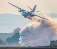During a flyby, CalFire Tanker 79 cleans out the tanks at Hollister Municipal Airport before heading back to Sacramento for the winter.