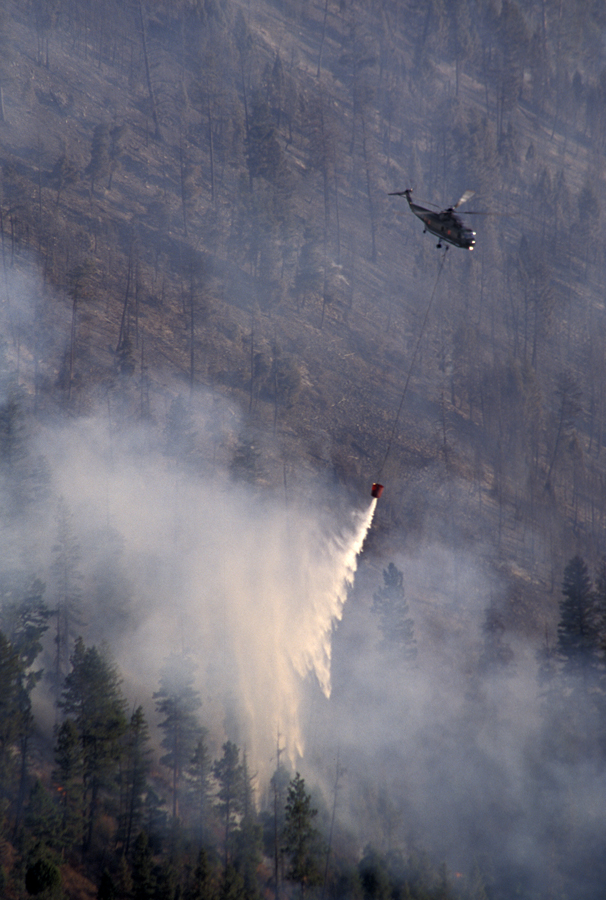 A helicopter makes a water drop on the eastern flank of the Bear Fire.