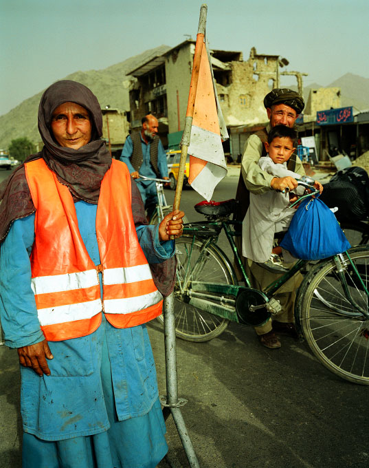 Bebe Gul Gholamri, 40 years old, directs traffic around a construction site in the Karte Se neighborhood of Kabul, Afghanistan. She is one of the four - woman road crew repairing the roads of the Afghan capital. All four women are widows.