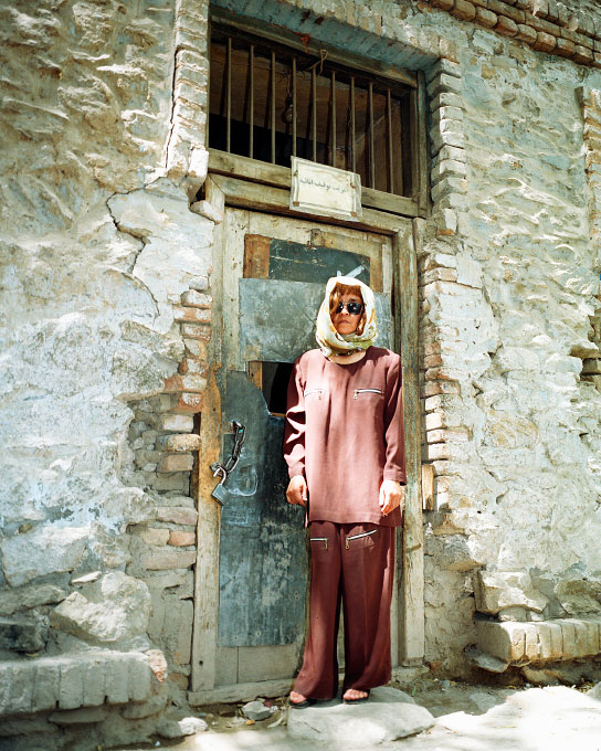 Suhila Fanoos, 25 years old, Welavate Women's Prison guard standing in front of the Women's prison holding 32 female inmates for crimes such as skipping home and leaving their family responsibilities. Sign above her head reads {quote}Prison of Women{quote}. Photographed in Kabul, Afghanistan on July 19, 2003.