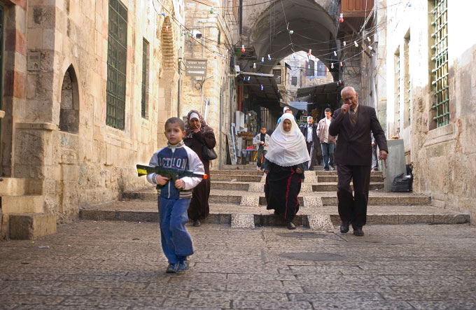 Young Palestinian boy carrying a toy machine gun walks through the street s of the Arab quarter of the Old City in Jerusalem, Israel on November 22, 2005.