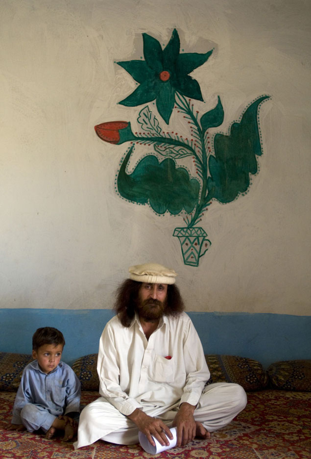 Bir Baba, (right) with his son  Tarek(left), a Pakistani refugee who fled his village in Bajaur when he received a threat from the Taliban saying they would kill him if he did not leave.  Bir Baba was the Malek, (tribal chief) of his village and is now the leader of a Pakistani refugee community which he set up on the edge of Islamabad, Pakistan.  There are now 70 -80 undocumented refugee families living in this community.