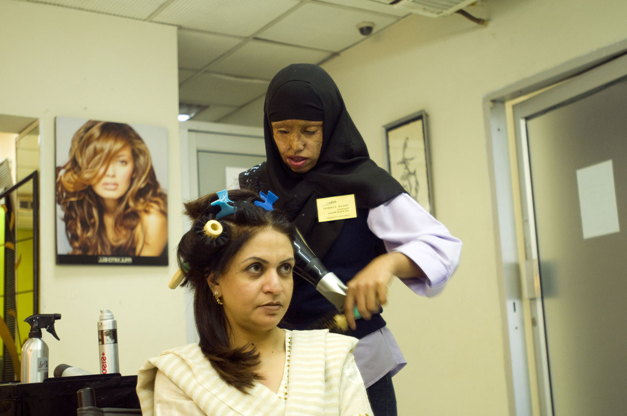 Saira Liaquat, 22yrs, burn victim and survivor, working on client, Mrs. Ishaq's hair at the Depilex beauty salon in Lahore, Pakistan on February 7, 2009. Saira is presently working as beautician at the Depilex beauty salon in Lahore, Pakistan.  There are presently over 300 cases of burn victims registered in Pakistan.  Most victims are between the ages of 14 - 25 years old.  Motives vary,  but are most frequently obsession, jealousy, suspected infidelity, husband wanting to re-marry, sexual non-cooperation.    The face and genitalia are the areas most generally targeted, those guaranteeing complete disfiguration.