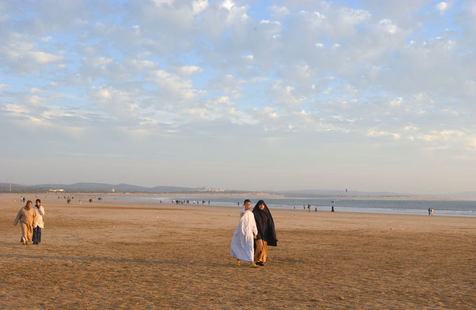 Young couple walking down the beach in Essaouira, Morocco.
