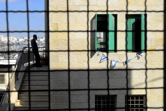 View of Israeli settlers from inside a cage built around a Palestinian home in Hebron.  The cage was built to protect the Palestinian family from rotten food and stones that were being thrown at them by the settlers.