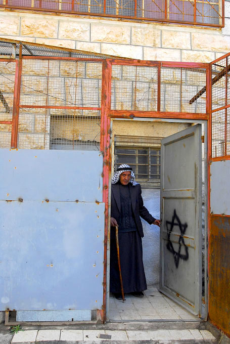 Palestinian man standing in front of his home where a cage was recently built around it to protect his family from Israeli settlers throwing rotten food and stones at them.  The settlers have also graffitied his door with a Jewish star.