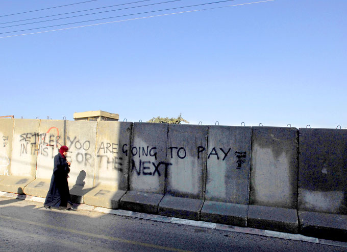 Palestinian woman walks by graffiti in the palestinian side of Hebron (H2) telling Israeli settlers that they will pay in the end.