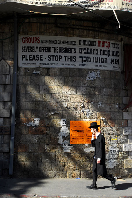 Young ultra orthodox jewish boy walking under an unwelcoming sign in Mea Sharim, a very conservative jewish neighborhood in Jerusalem.
