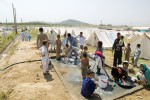 Refugees from Swat bathing and washing their clothes and one of the water springs set up at the Swabi IDP camp in Swabi, Pakistan on May 20, 2009.  There are now 1.5 million displaced people in Pakistan's North West.