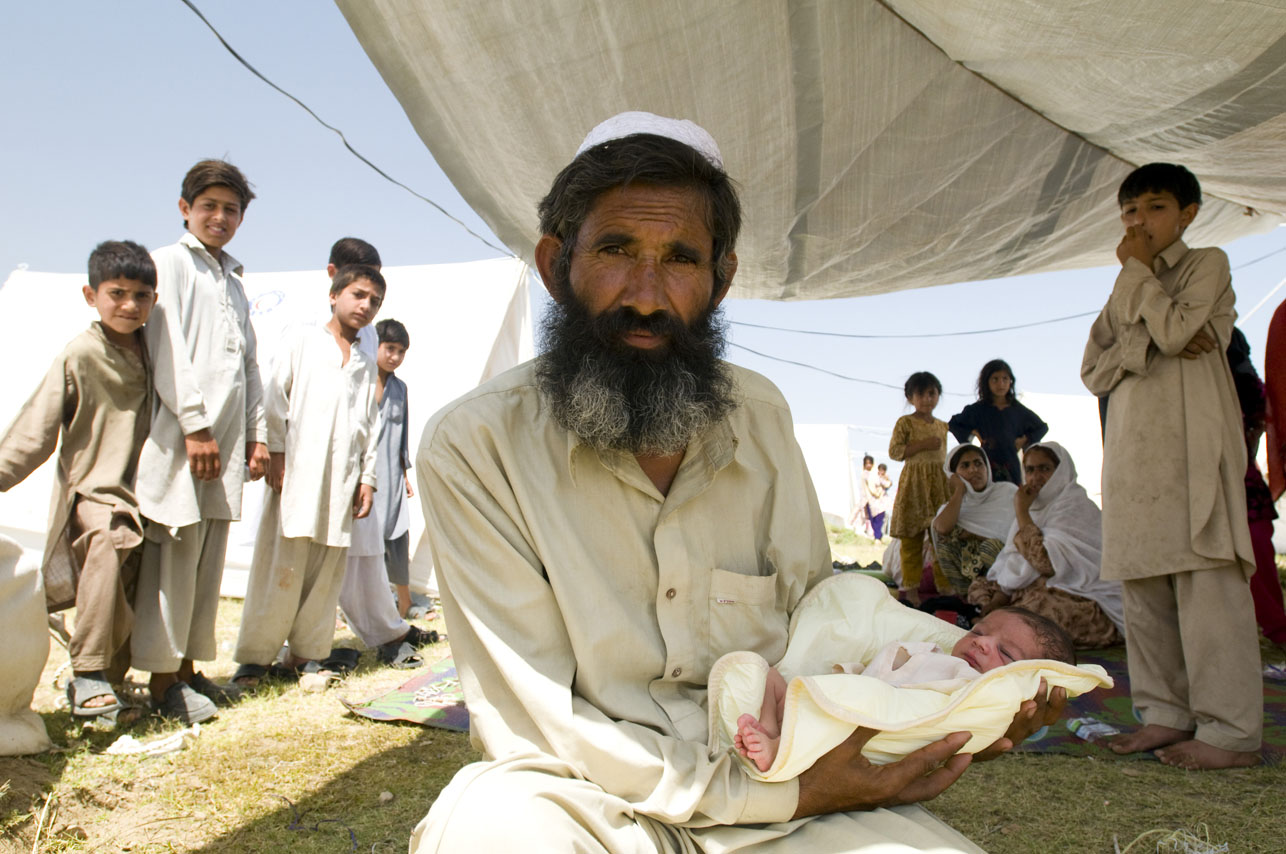 Said Wahid holding his newborn grandson, Sahil under his tent at the Swabi IDP camp in Swabi, Pakistan.  Sahil was born 3 days ago, just a few days after this refugee family had fled Swat and moved to the IDP camp for safety.  Photographed in Swabi, Pakistan on May 20, 2009.  There are now 1.5 million displaced people in Pakistan's North West.