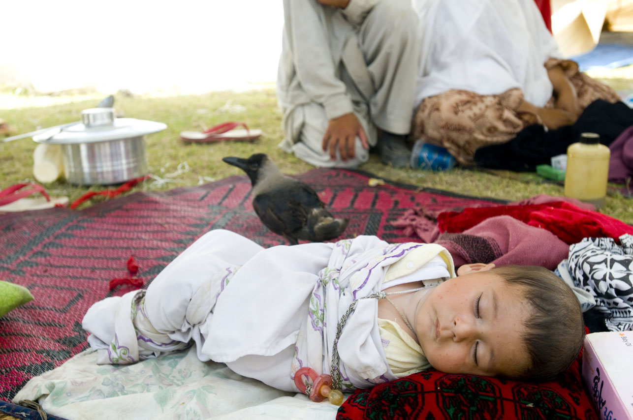 Refugee baby lying outside the family's tent as a crow stands by at the Swabi IDP camp in Swabi, Pakistan on May 2009.  There are now 1.5 million displaced people in Pakistan's North West.