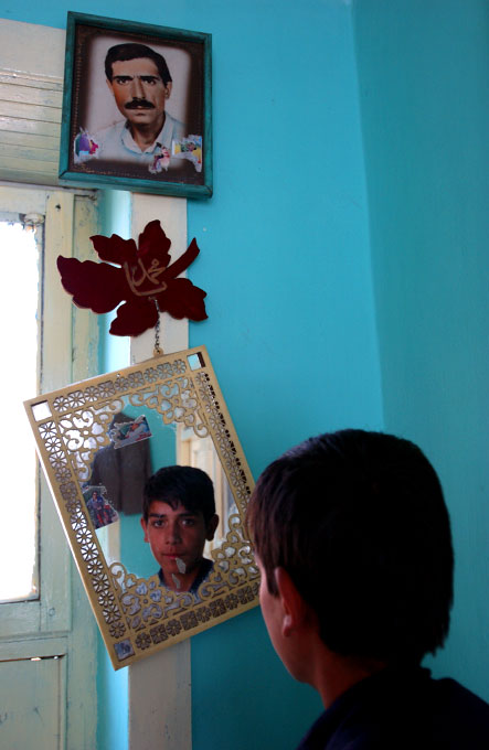 Portait of a young Afghan boy looking in the mirror while an old photograph of his father stares back at us.