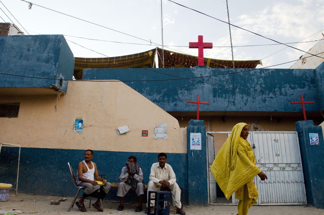 Pakistani woman walks by a group of men playing cards infront of a church in the France Christian Colony in F7/4 Islamabad, Pakistan on August 19, 2008.  Christians make up only 1.5% of the population of Pakistan, a country which is 97% Muslim.  Christians living in Pakistan face serious problems, including unequal employment and education opportunities, and poor housing facilities.  Many are scared go by their Christian names or to wear physical symbols of their faith in fear that they will be charged with blashemy for defaming Islam.