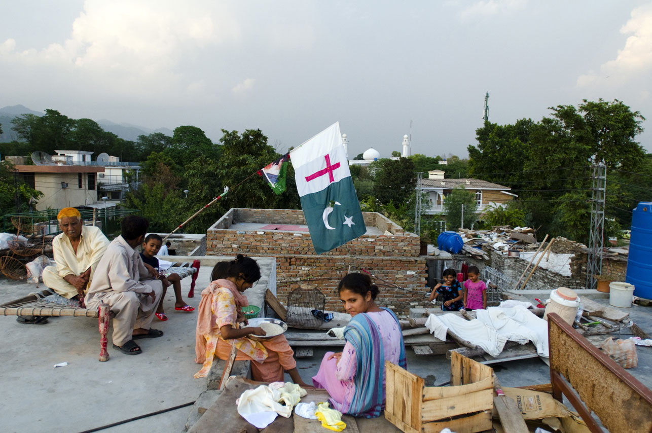 Christian Pakistani family sitting on their roof in front of a Pakistani Christian flag inside the France Christian Colony in F7/4 Islamabad, Pakistan on August 19, 2008.  Christians make up only 1.5% of the population of Pakistan, a country which is 97% Muslim.  Christians living in Pakistan face serious problems, including unequal employment and education opportunities, and poor housing facilities.  Many are scared go by their Christian names or to wear physical symbols of their faith in fear that they will be charged with blashemy for defaming Islam.