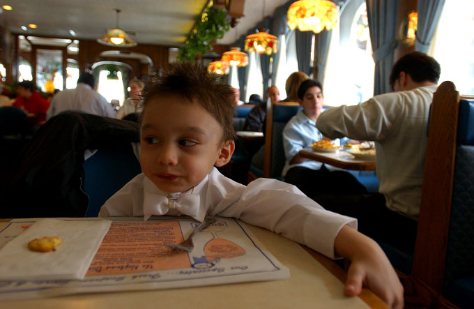 Young American Gypsy boy having lunch at a local diner in Queens, NY right after he was baptised.