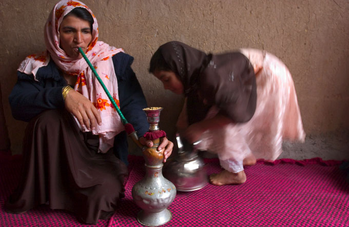 Afghan woman smoking a sheesha pipe at her home in Herat, Afghanistan on March 16, 2005. This tradition in Herat comes from neighboring Iran where the sheesha pipes are quiet common. However, it is rare in Afghanistan to see a woman ever smoking.