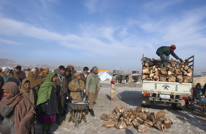 Returning Afghan refugees line up for wood distribution at the Chamany Babrak refugee camp in Kabul, Afghanistan. This winter in Afghanistan has been the coldest in years.  The cold weather  poses the largest threat to the refugee communties living in small tents with little heat.  Photographed in Kabul, Afghanistan