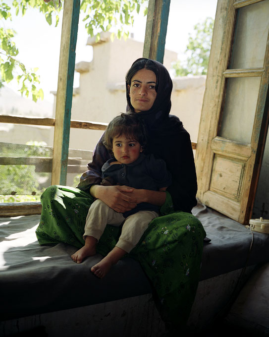 Freeshta Sadat, 19, deaf and dumb mother of Zubaida (on her lap) in her parents' home in Qargha, Afghanistan. She was rescued by her father from an oppressive and violent marriage. Her husband, a conservative Pashtun from Eastern Afghanistan, once was a driver for the Taliban. After they got married, her husband's family tied her down and tatooed her face with traditional markings when she refused to oblige.
