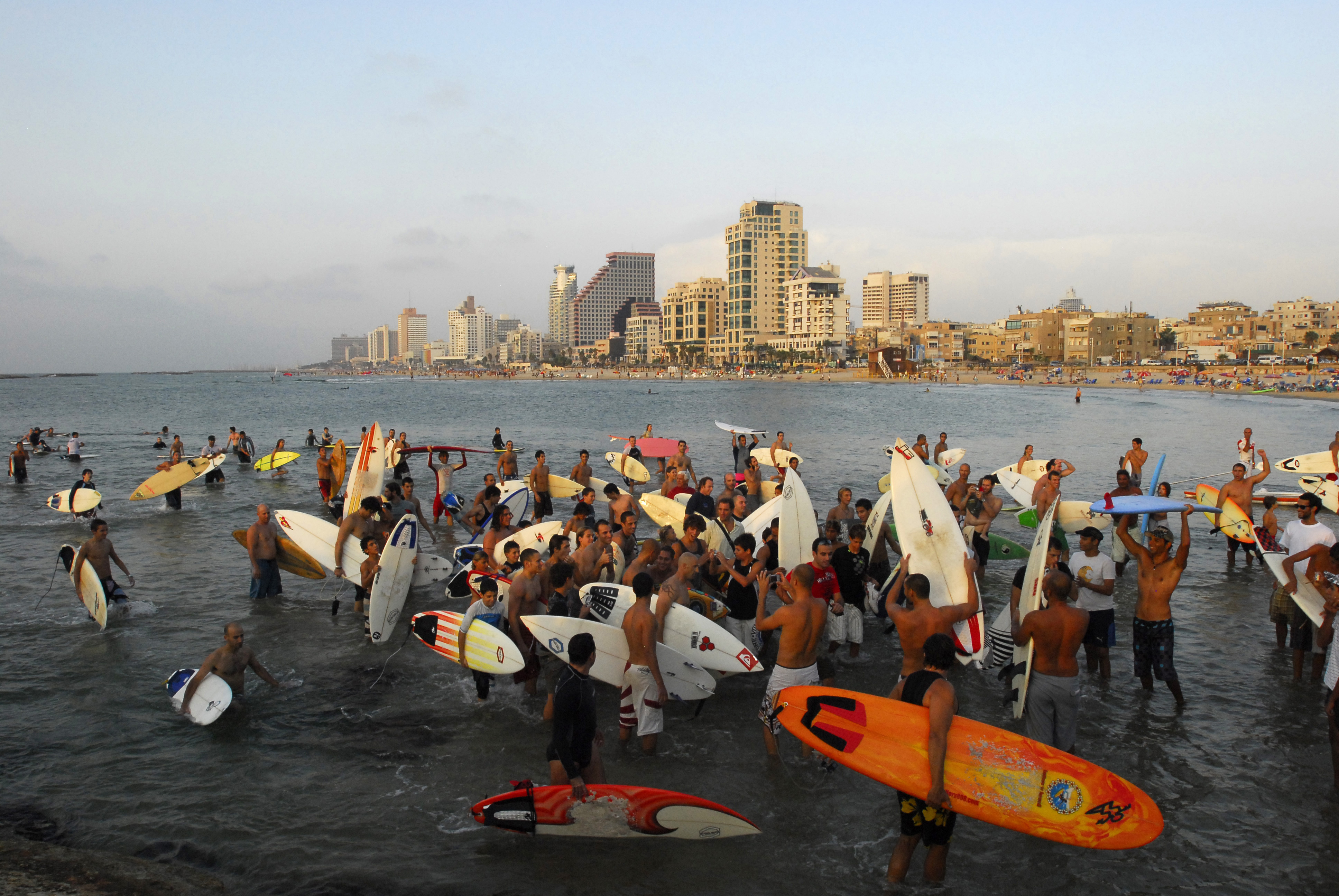 Kelly Slater's fans chase him up out of the water after a Surfers Circle in Tel Aviv, Israel.