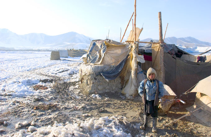 A young Afghan refugee at Chaman-e-Babrak refugee tent camp stands outside his home in the freezing cold.   Many refugees are homeless rural people who cannot be relocated to the countryside.  At least 18 have already dided this winter in Afghanistan.