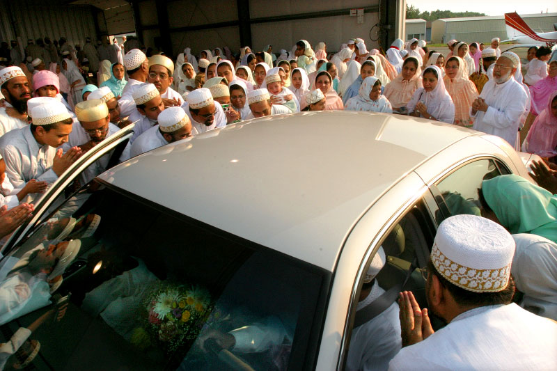 As Dr. Burhanuddin's car departs the welcoming ceremony at Lawrence Municipal airport, his followers pay their respects and get on last glimpse.