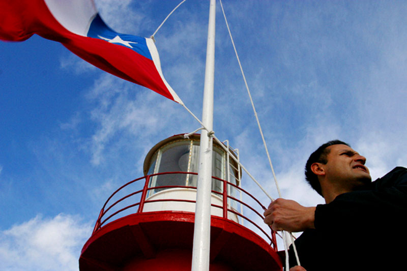Navy officer Miguel Saez raises the national flag every morning at the Espiritu Santo Lighthouse, situated on a remote tip of Patagonia, Chile.