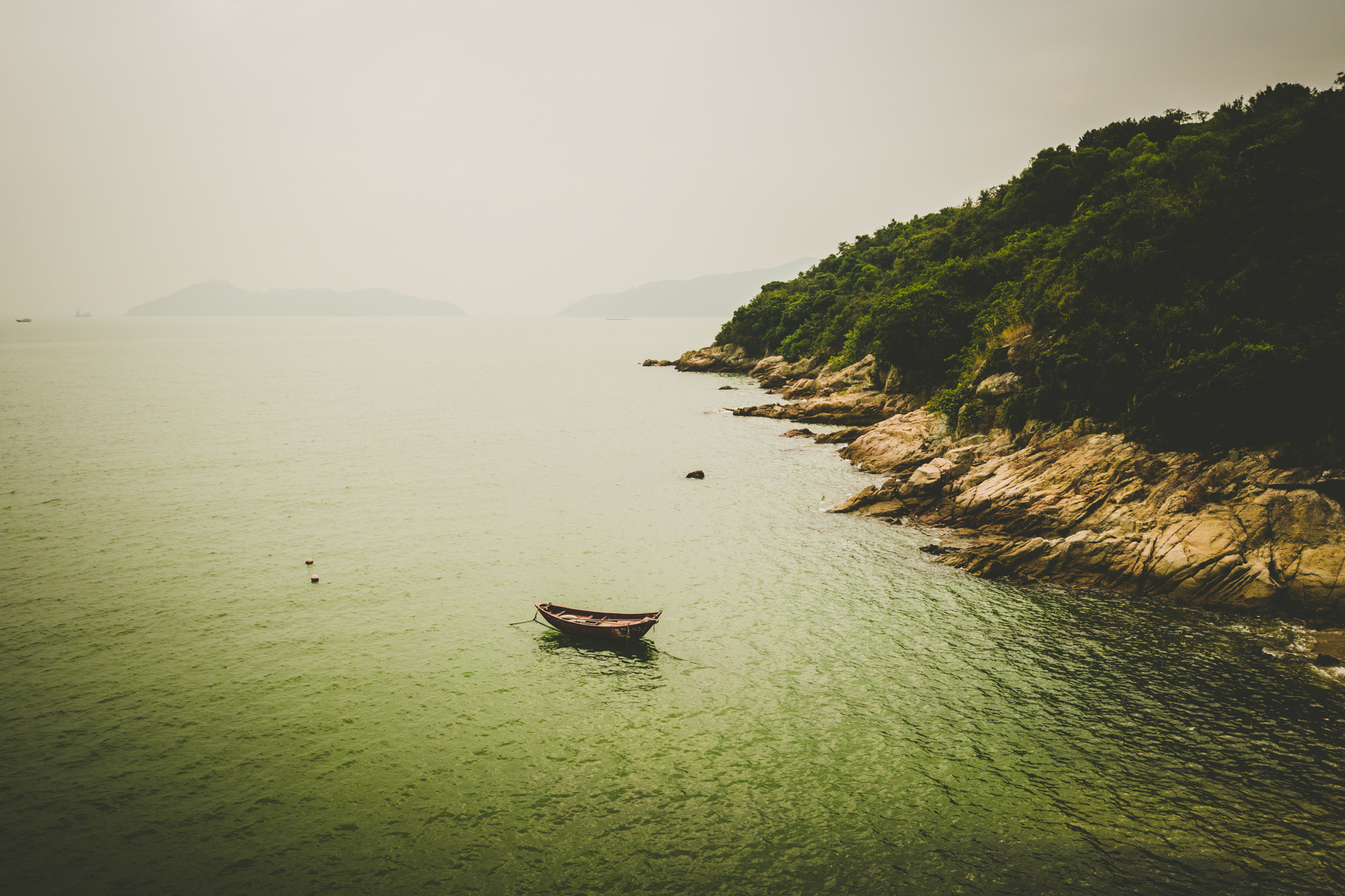 A lone rowboat tied to the shore on Lantau Island, Hong Kong.