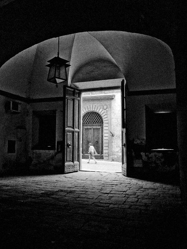 A woman walking down a narrow quiet street is framed in an ancient doorway.