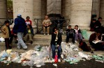 Tourists, pilgrims and the faithful sit amid trash left behind after over 350,000 people filled St. Peter's Square for the Mass for the Inauguration of Pope Benedict XVI on Sunday, April 24, 2005 in Rome, Italy.