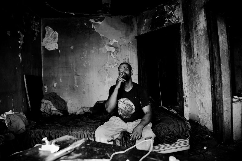 42 year-old  Detroit squatter Kevin Smith smokes in the abandoned house where he live. Many, like Kevin, become squatters as the town face the severe economic downtown.
