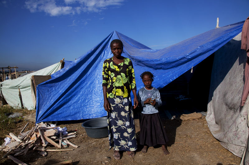 At Pont-Rouge refugee camp, 36 year old Haitian earthquake survivor Salomon Vilme and her 7 year old daughter Chrisla stay at their tent where 5 family members live together.