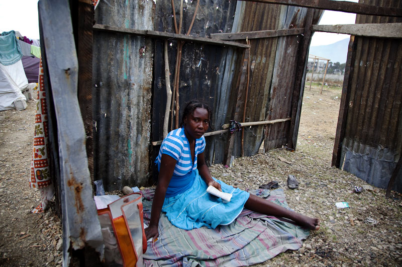 With a copy of bible, 34 year old Haitian earthquake IDP Marie Mylene Marcelin stays at her shelter at Pont-Rouge refugee camp.