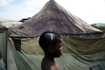 Head injured 12 year Haitian quake IDP Fedner Seraphin in front of his tent at Pone Rouge refugee camp.
