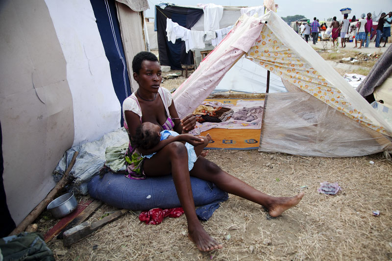At Pone Rouge refugee camp, 23 year old Haitian quake survivor gives mother milk to her 7 month old baby Nadia next to her tent where she and 4 other family members live together. She lost her husband, brother, sister and other baby due to the January 12th earthquake.