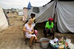 At Pont-Rouge refugee camp, 19 year old  albino Linda Colas is cared for her braid hair by her 27 year old friend Marie France Thomas, who stays next to her 48 year old relative Marie Louroes , in front of their tent. All of the three are the survivors of the January 12th earthquake.