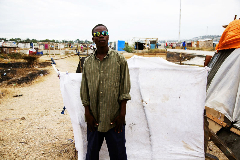 Loner Stmail, 15 year old Haitian earthquake IDP, in front of his tent at Pont-Rouge refugee camp. He lost a cousin due to the January 12th quake.