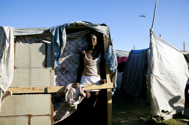 At Pont-Rouge refugee camp, 18 year old Haitian earthquake survivor Vaniola Paul stays at her tent where 4 family members live together, as a US military helicopter flies. She lost her brother in law due to the quake.