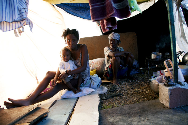 At Pont-Rouge refugee camp, 20 year old Haitian earthquake survivor Marie Flore Antoine holds her 1 year old baby Louishel Bazil, as her 60 year old relative Marie Antoine stays nearby in the tent where they and 6 other family members live together. Marie Flore lost 5 relatives, including her daughter, due to the quake.