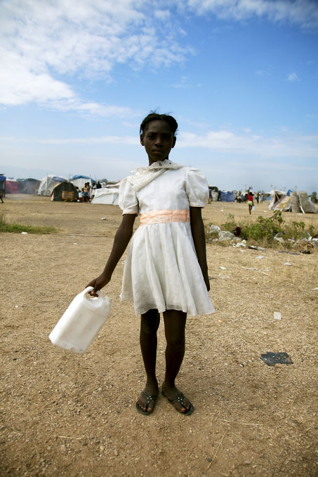 At Pont-Rouge refugee camp, 12 year old Haitian earthquake survivor Betina Paul stands with a water bottle container. She lost her uncle due to the quake.