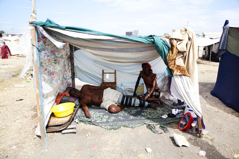At Pone Rouge refugee camp, Remond Victor, 67,  Haitian IDP with the broken leg due to the January 12th quake, and his 45 year old relative Mona Appollon stay at their tent where 3 people live together.