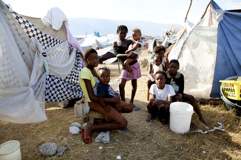 At Pont-Rouge refugee camp, Haitian earthquake survivors of the Petitfrere family stay next to their tent where 10 family members live together.