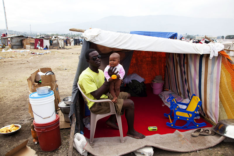 At Pone Rouge refugee camp, 24 year old Haitian quake IDP Jean Renald Celestin holds his 5 month old baby Sarah at his tent where his wife also lives. He lost his brother and sister due to the January 12th earthquake, and Christella lost her aunt.