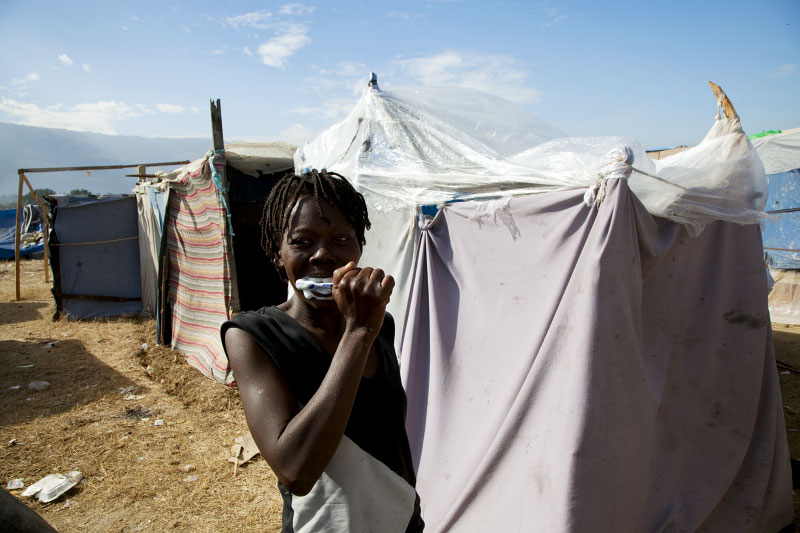 At Pont-Rouge refugee camp, 36 year old Haitian earthquake survivor Carline Toussaint brushes teeth in front of her tent where 6 family members live together. She lost her sister and brother due to the January 12th earthquake.