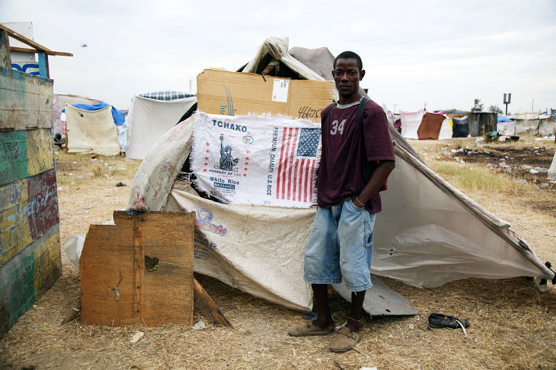At Pont-Rouge refugee camp, Jeune Wadsonn, 24 year old Haitian earthquake IDP, stands in front of his tent where he and his 2 sons and 6 sisters live together.